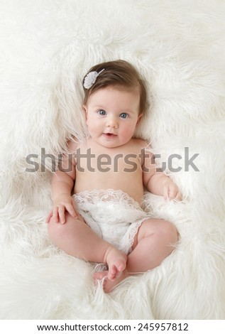Newborn baby girl posed in a bowl on her back, on blanket of fur, smiling looking at camera - stock photo