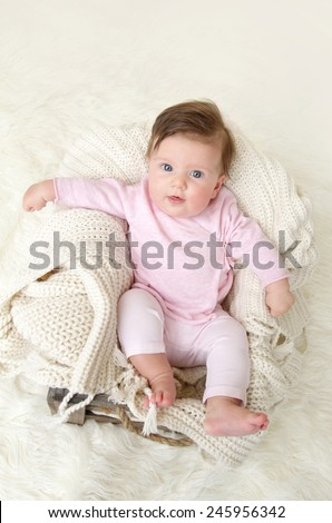 Newborn baby girl posed in a bowl on her back, on knit blanket, smiling looking at camera, wearing comfortable pj pajamas - stock photo