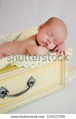 Newborn baby girl sleeping in a vintage yellow drawer.