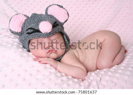 Newborn baby girl sleeping wearing a mouse hat. - stock photo