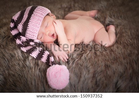 Newborn baby girl sleeping wearing brown and pink hat, on fur and white background. - stock photo
