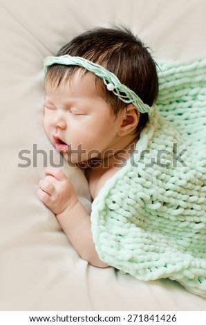 newborn baby girl sleeping with open mouth under a green knitted blanket