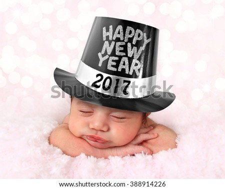 Newborn baby girl wearing a Happy New Year  2017 hat.