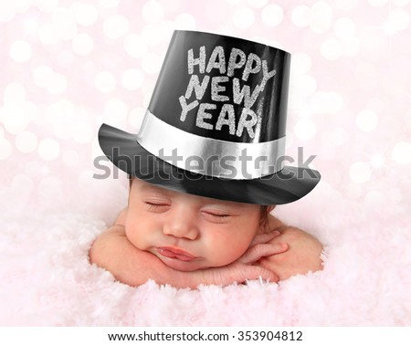 Newborn baby girl wearing a Happy New Year hat with a festive bokeh background.