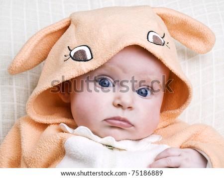 Newborn baby girl wearing easter bunny costume on light background - stock photo