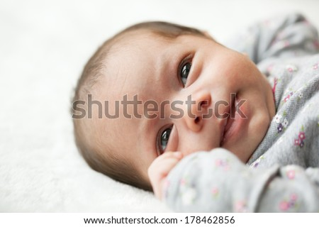 Newborn baby girl 6 weeks old with eyes open laying on a blanket