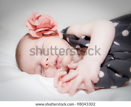 Newborn baby girl with flower sleeping - stock photo