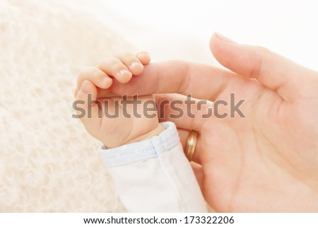 Newborn baby hand holding mother finger, new born kid and parent - stock photo