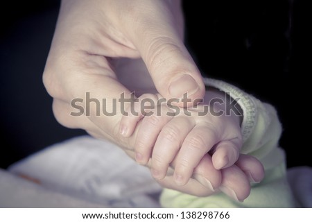 Newborn Baby hand holding mother's finger - stock photo