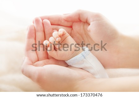 Newborn baby hand in mother hands. new born kid and parent help assistance concept  - stock photo
