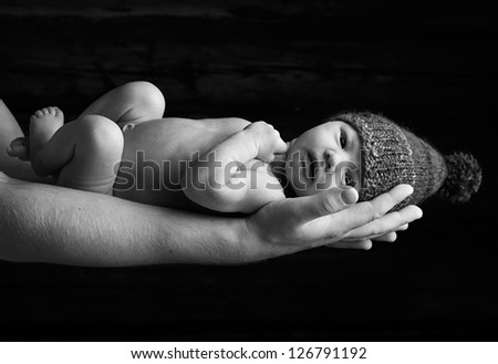 Newborn baby hat in fathers hands, black and white - stock photo