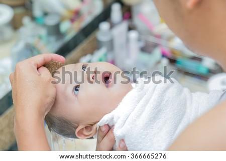 Newborn baby having a bath ,have fun in the bath time - stock photo