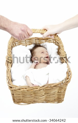 Newborn Baby Held In Basket By Parents