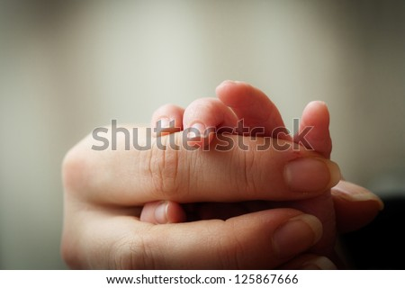 Newborn baby holding his mothers finger, selective focus - stock photo