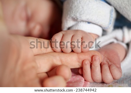 Newborn baby holding the hand of an adult