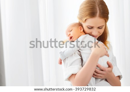 newborn baby in a tender embrace of mother at the window