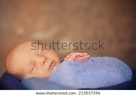 Newborn baby in basket - stock photo
