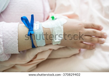 Newborn baby in hospital with identification bracelet tag name - stock photo