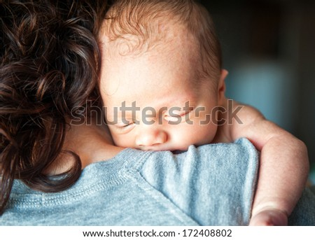 Newborn baby in the arms of his mother - stock photo