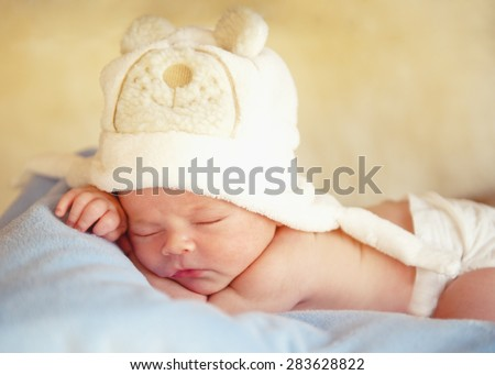 Newborn baby in the cap bear sleeps. - stock photo