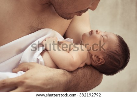 Newborn baby in the hands of his father.Parenting concept