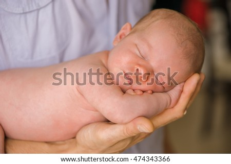 newborn baby in the hands of the young dads