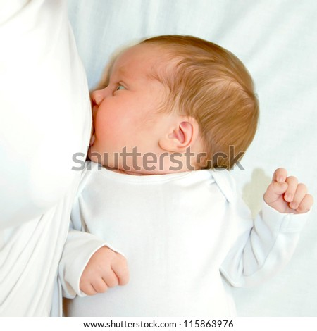 Newborn baby is breast feeding closeup. Selective focus on the baby face. - stock photo
