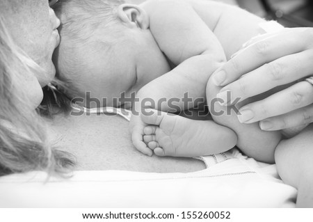 Newborn baby is holding his foot while asleep on mother's chest - stock photo