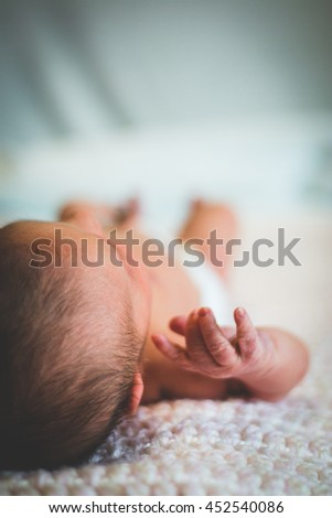Newborn baby laying on bed in hospital