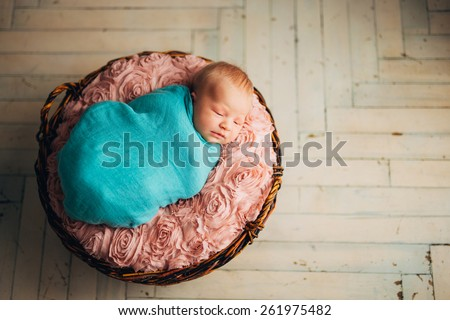 Newborn baby lying in a basket - stock photo