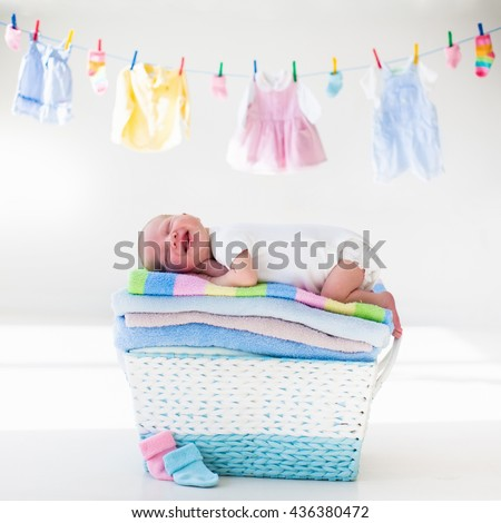Newborn baby on a pile of clean dry towels. New born child after bath in a towel. Family washing clothes. Kids wear hanging on a line. Infant apparel, textile for children. Smiling boy after shower.  - stock photo
