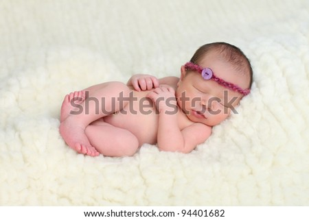 Newborn baby on sheep wool, mix race: Caucasian and Asian - stock photo