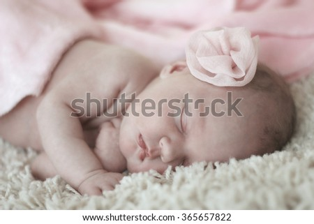 Newborn baby peacefully sleeping under a pink blanket