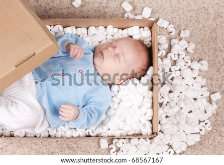 Newborn baby represented in post box with filler. Small baby sleeping among filler. Little newborn baby will be delivered to his parents. - stock photo