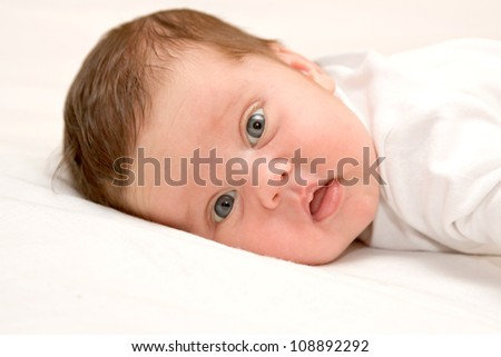 Newborn baby's face close up. Kid is very surprised and dissatisfied, wide-open eyes and mouth.