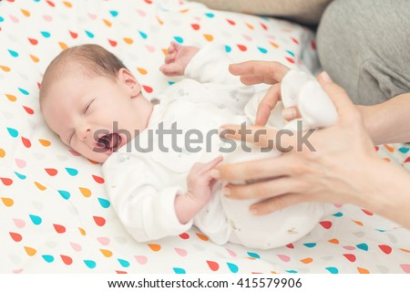Newborn baby screaming in pain with colic; mother helping her to bend her knees to ease pain in stomach - stock photo