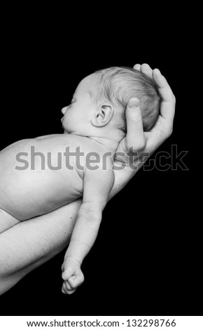 Newborn baby sleep in A Father hands. Black-and-white photo