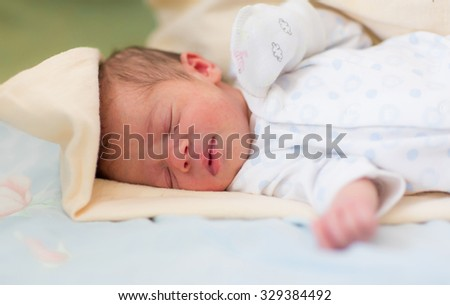 Newborn baby sleeping, 3 days old at home, soft focus,shallow DOF - stock photo