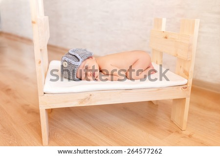 newborn baby sleeping in a baby cot