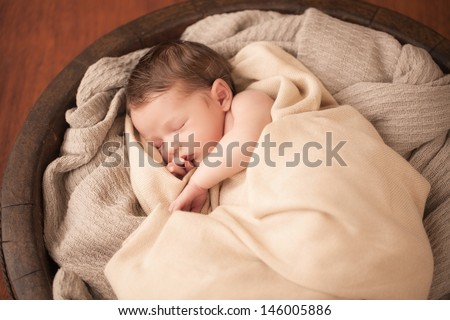 Newborn baby sleeping in a wooden bowl - stock photo
