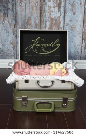 Newborn baby sleeping in suit case - stock photo