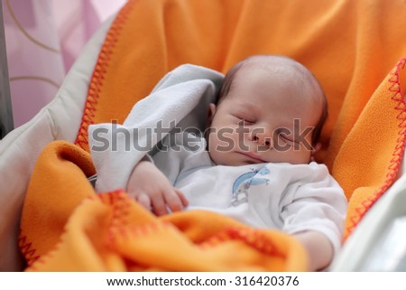 Newborn baby sleeping in the chair on the orange blanket - stock photo