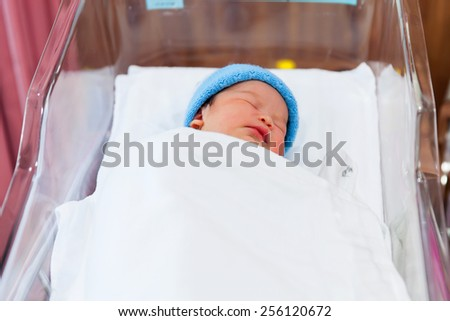 Newborn baby sleeping in the delivery room. - stock photo