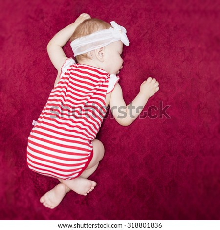 newborn baby sleeping on a red blanket - stock photo
