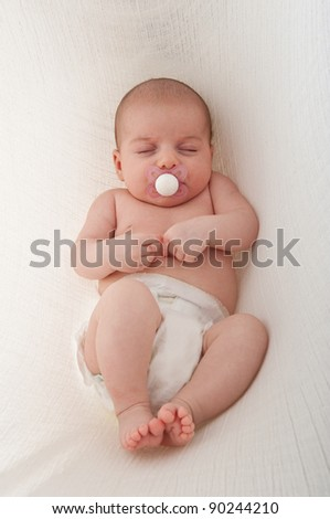 Newborn Baby sleeping on a white background. Hanging in cotton sling.
