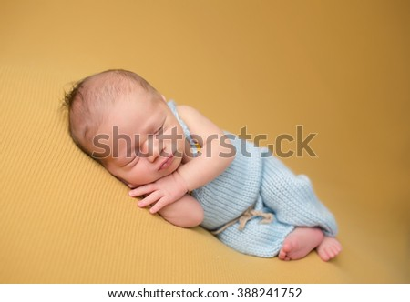 Newborn baby sleeping on blanket, asleep, posed, in knit outfit; parenting concept.