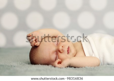 Newborn baby sleeping on blue blanket. Soft focus, very shallow DOF. - stock photo