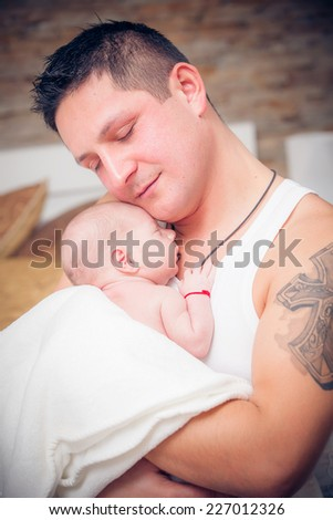 Newborn baby sleeping on the shoulder of his father - stock photo