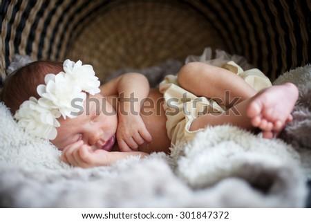 Newborn baby sleeping on white blanket - stock photo