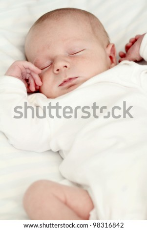 Newborn baby sleeping on white blanket. Soft focus, very shallow DOF. - stock photo